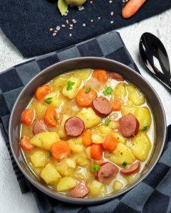 Ein Kartoffel Eintopf mit Möhren und Rindswurst in einer grauen Schale angerichtet und auf einem Küchenhandtuch fotografiert