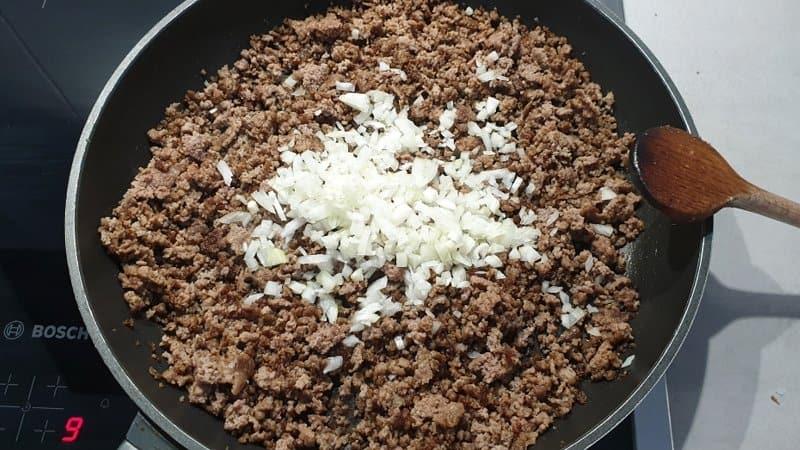 Hackfleisch in einer Pfanne krümelig angebraten mit Zwiebel Würfel.