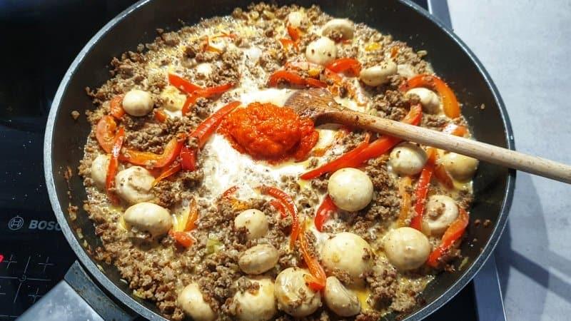 Jetzt gibst du Ajvar in die Pfanne und lässt das ganze einmal aufkochen. Die Hitze reduzieren und bei geringer Hitze köcheln lassen.