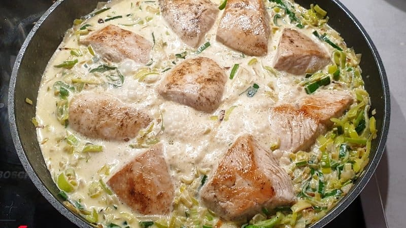 Die Puten Medaillons in die Lauch-Rahm-Soße geben. Offen für 8-10 Minuten in der Soße gar ziehen lassen.
