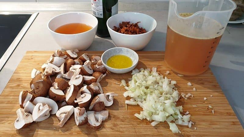 Die Vorbereitung für die feine Pilz-Creme-Suppe: Die getrockneten Pilze gründlich abspülen und anschließend mit ca. 200 ml warmen Wasser übergießen und einweichen lassen. Tipp: Mindestens eine Stunde einweichen. Am besten aber über Nacht einweichen. Das Wasser bitte nicht wegschütten. Nach der Einweichzeit durch ein feines Sieb geben und für die Suppe weiterverwenden. Die Champignons putzen und vierteln. Die Zwiebel schälen und fein würfeln.
