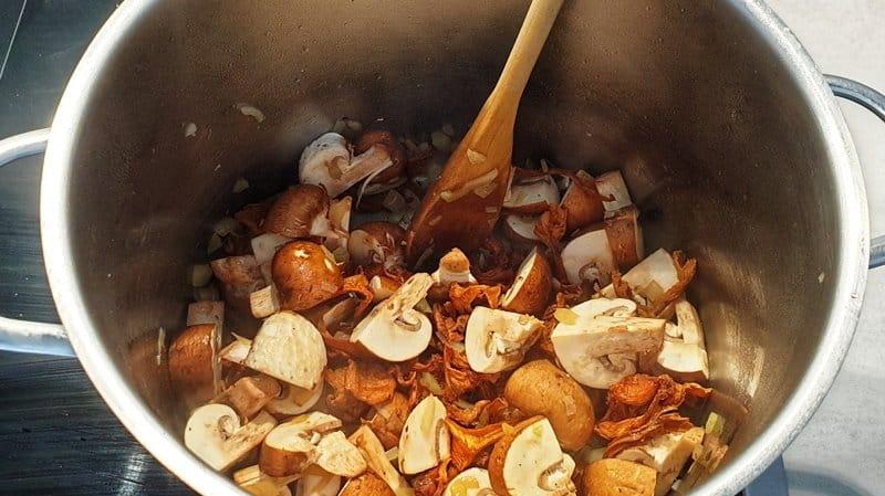 Anschließend die Pilze mit in den Topf geben und mit andünsten.