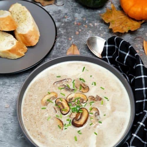 Pilz-Creme-Suppe dekorativ angerichtet in einer grauen Schale, mit ein paar Pilzen in der Mitte und frischem Schnittlauch angerichtet. Im Hintergrund herbstliche Dekoration und ein Kräuter Baguette