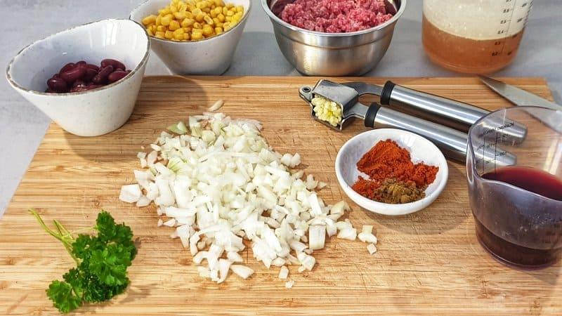 Die Zutaten für das Chili con Carne mit Rinderhack sind schnell vorbereitet. Zwiebel und Knoblauch schälen und fein haken.