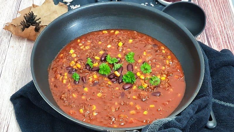 Das Chili con Carne mit Rinderhack wird mit etwas frischer Petersilie garniert und serviert.