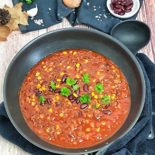 In einer Pfanne ein fertig gekochtes Chili con Carne mit Mais und roten Bohnen. Mit Petersilie bestreut.