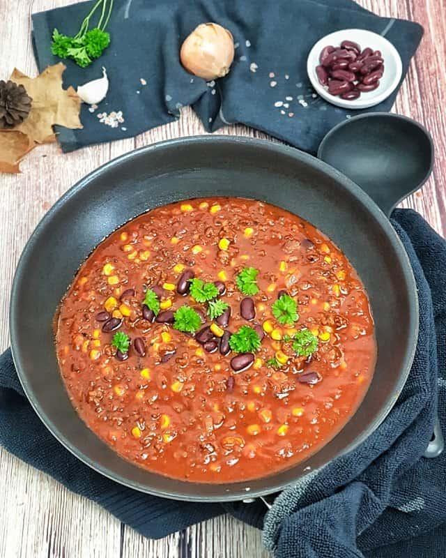 Chili con Carne mit Mais und Kidneybohnen in einer Pfanne angerichtet und mit Petersilie bestreut. Im Hintergrund eine Schale mit roten Bohnen und herbstliche Dekoration.