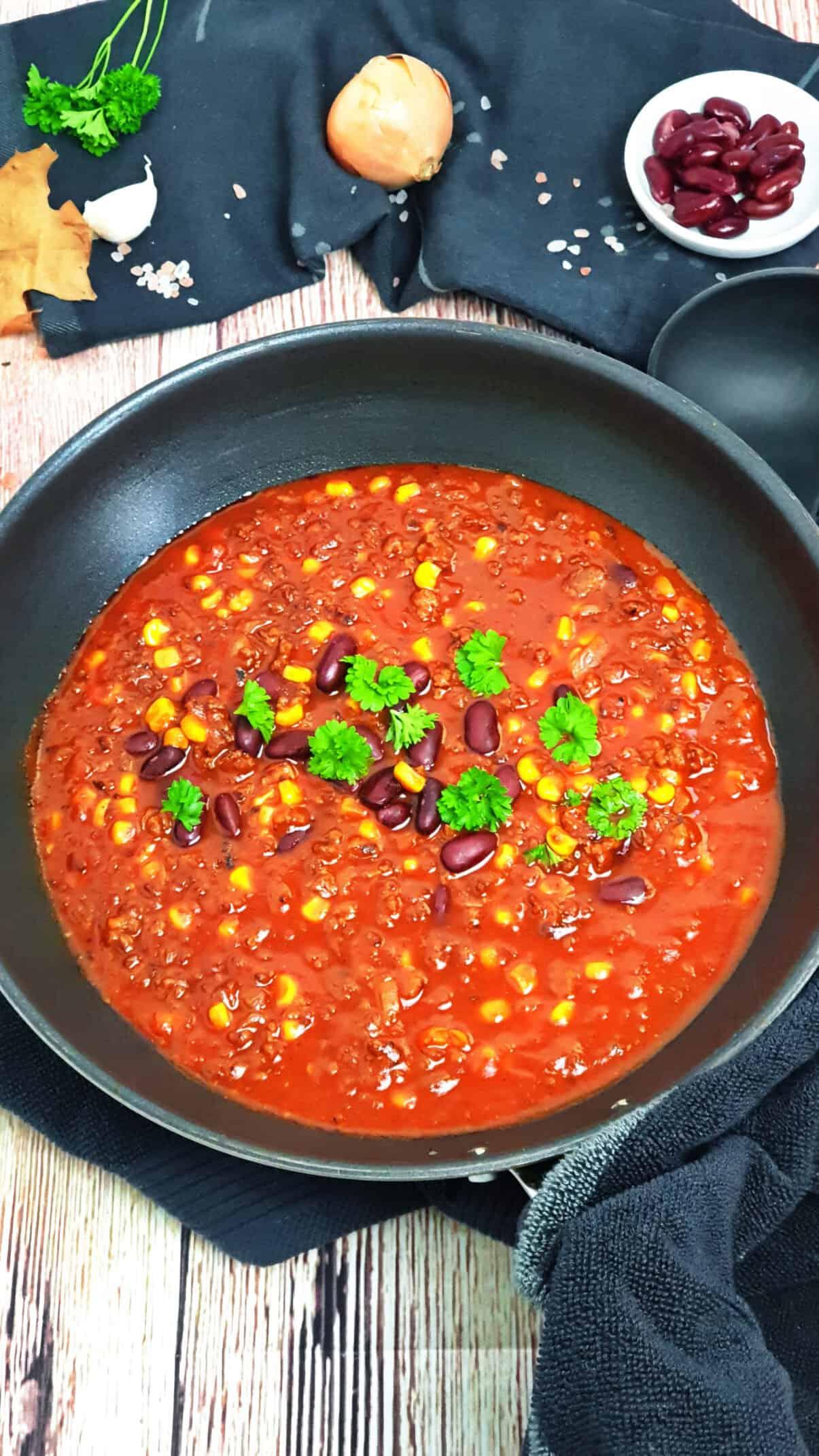 Chili con Carne in mit Hackfleisch, Mais und Bohnen einer schwarzen Pfanne.