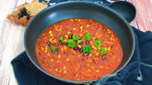In einer Pfanne ein Chili con Carne mit Rinderhackfleisch, Bohnen und Mais. Im Hintergrund Deko.