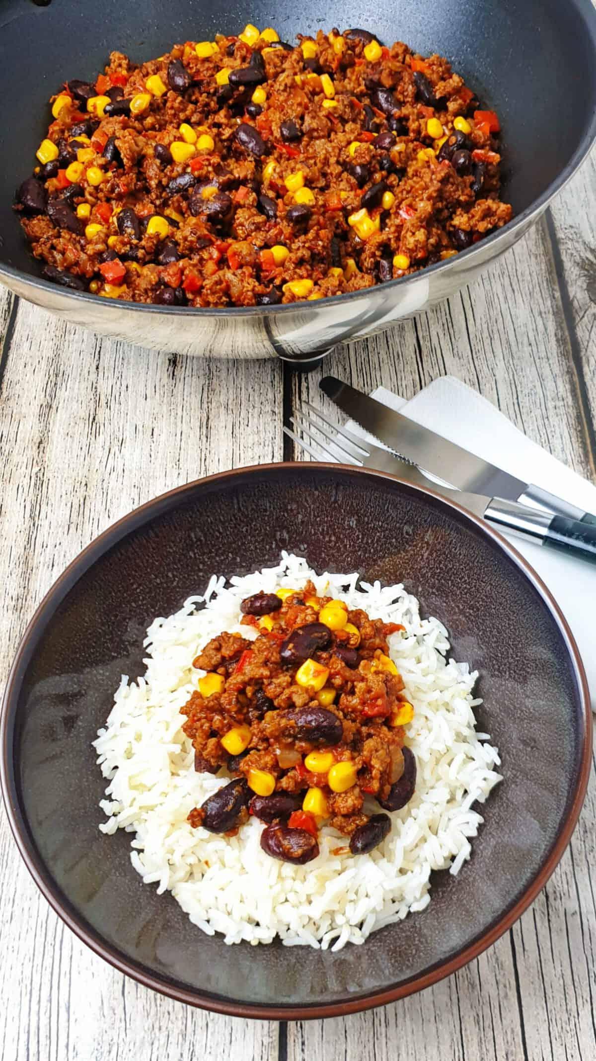 In einer braunen Schale Chili con Carne mit Reis. Im Hintergrund eine Pfanne mit Chili.