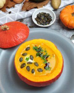 Kürbis-Suppe in einem Kürbis serviert. Mit Kürbiskernen und Kürbisöl garniert. Im Hintergrund herbstliche Deko.