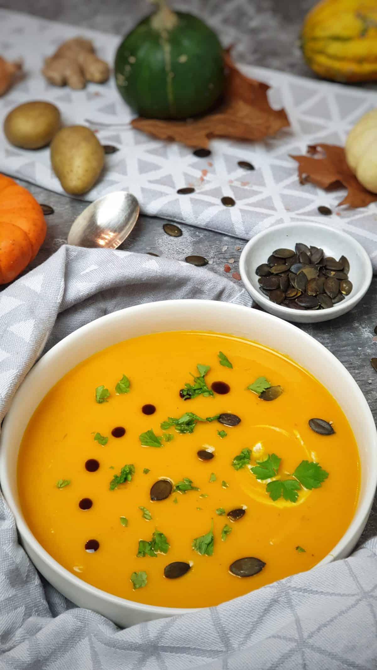 In einer weißen Schale eine Kürbis-Creme-Suppe mit Kürbiskernen und Kürbisöl. Im Hintergrund herbstliche Deko.