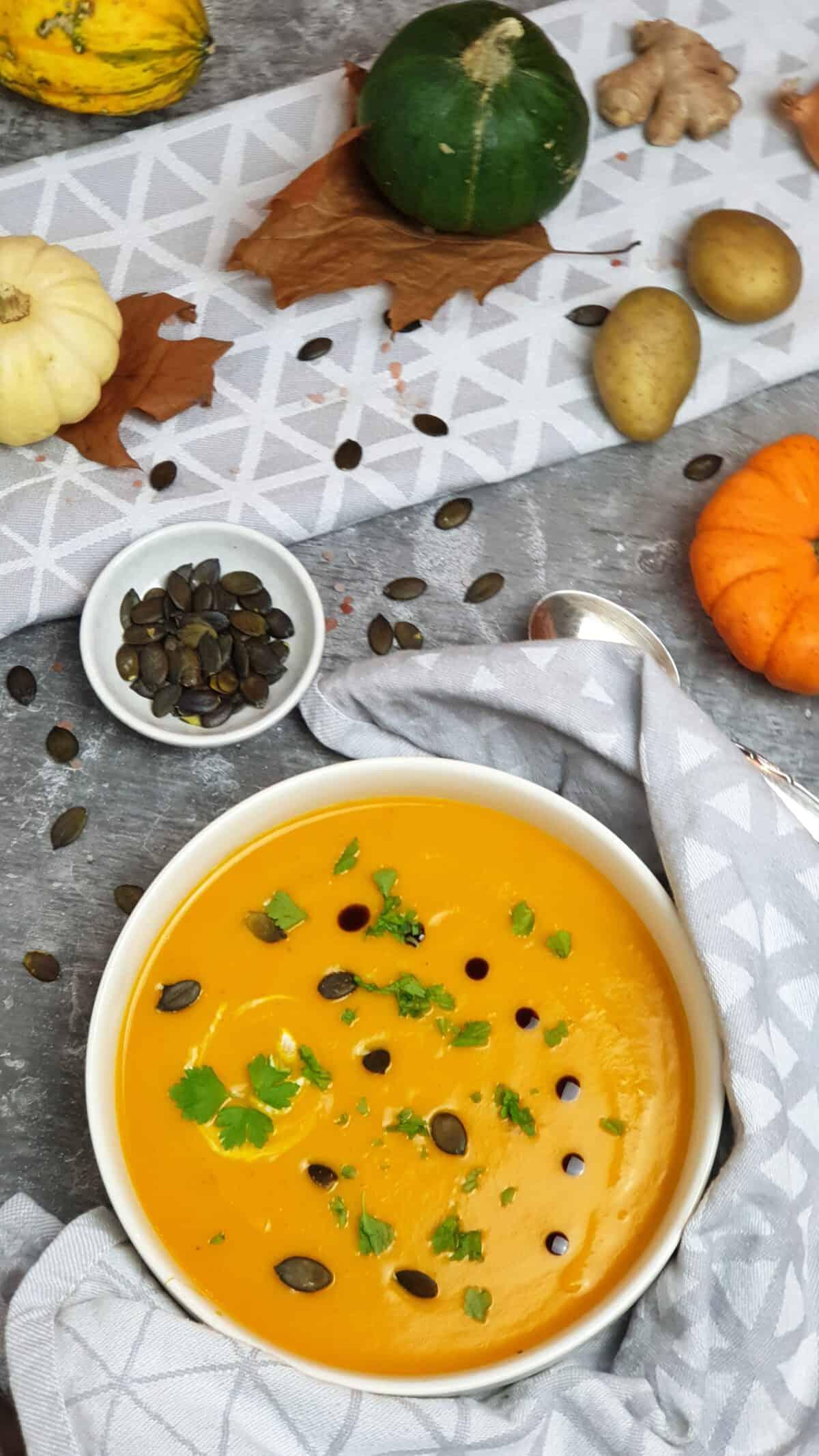 In einer weißen Schale eine Kürbis-Suppe mit Kürbiskernen und Kürbisöl. Im Hintergrund herbstliche Deko.