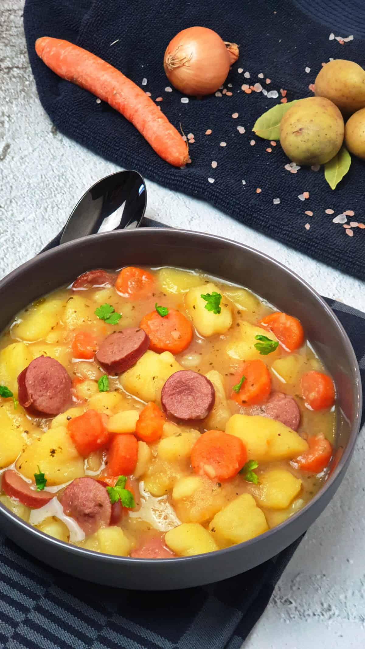 In einer grauen Schale ein Kartoffel-Möhren-Eintopf mit einer Frankfurter Rindswurst. Im Hintergrund Deko.