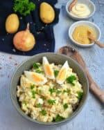 In einer grauen Schale angerichtet ein klassischer Kartoffelsalat mit Mayonnaise. Im Hintergrund Deko.