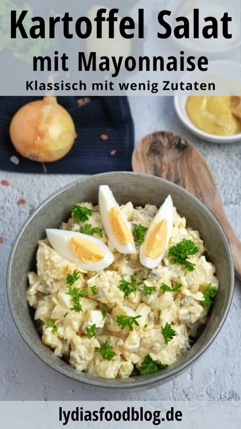 In einer grünen Schale angerichtet, ein klassischer Kartoffelsalat mit Mayonnaise. Auf dem Salat sieht man 3 Eier Spalten und im Hintergrund zu erkennen eine Zwiebel, ein Schälchen Mayonnaise und ein Schälchen Senf. Neben der Schale liegt ein Holzlöffel.
