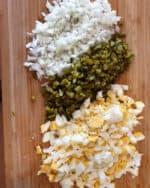 Auf einem Schneidebrett klein geschnittene Gurken, Zwiebeln und Eier.
