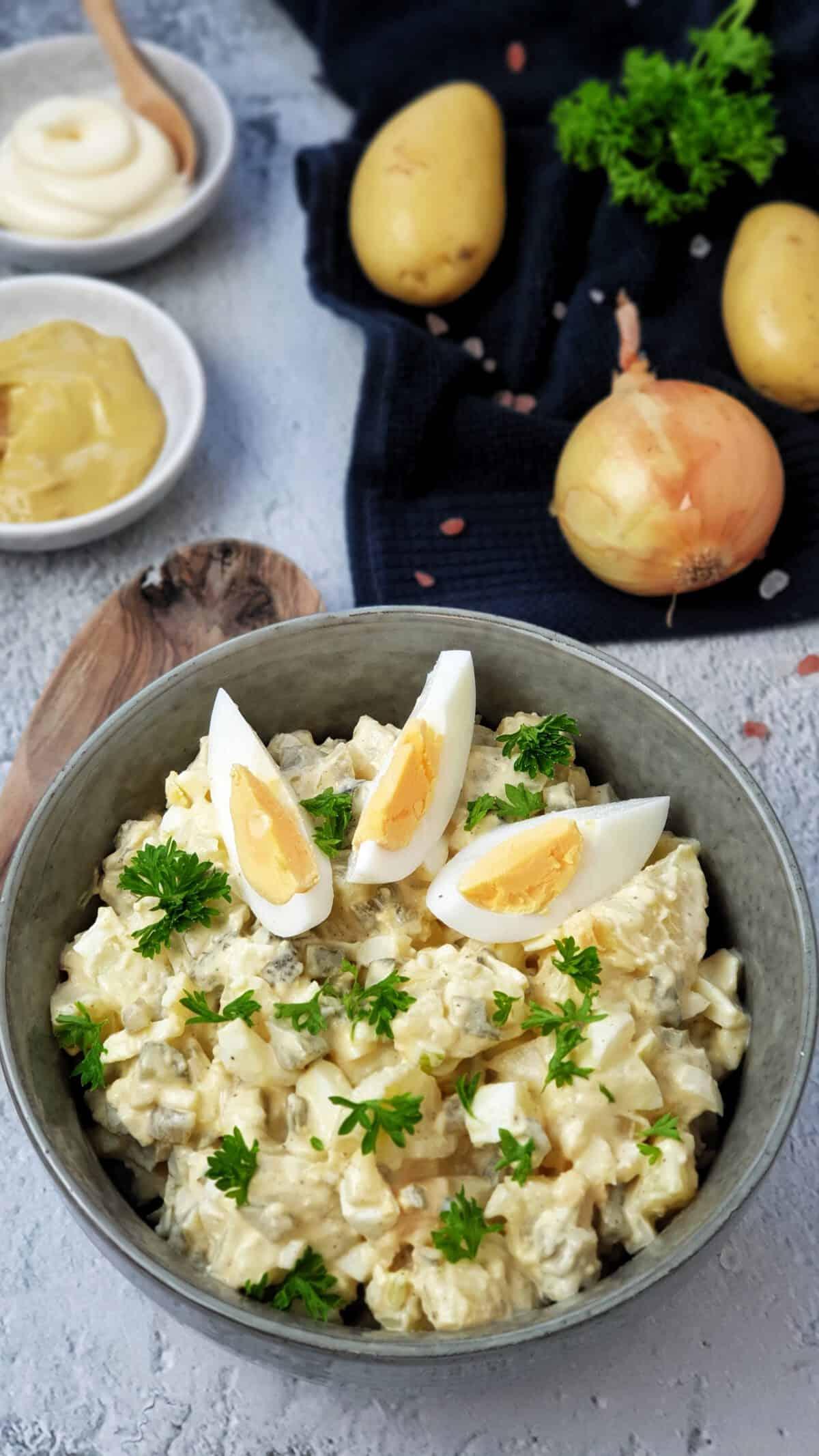 In einer graugrünen Schale angerichtet ein Kartoffel-Salat mit Mayonnaise und Ei.