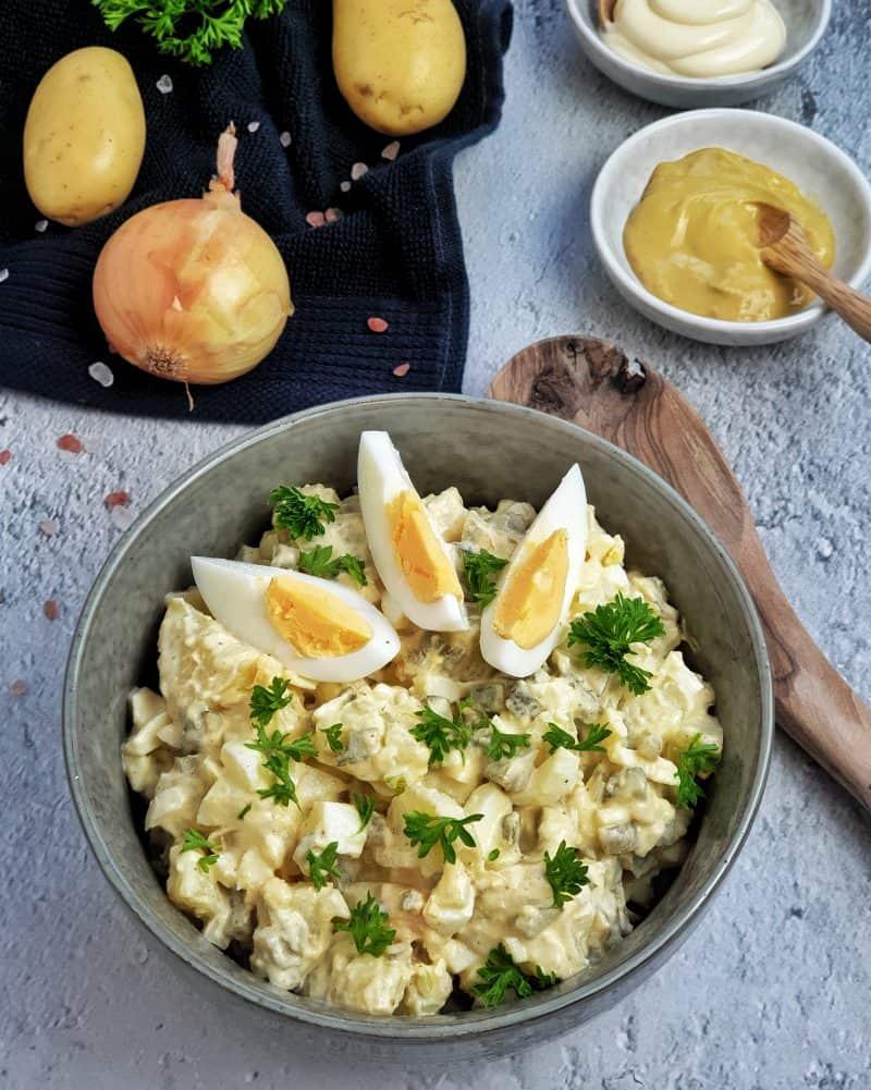 Klassischer Kartoffelsalat mit Ei und Gewürzgurken in einer Schale dekorativ fotografiert