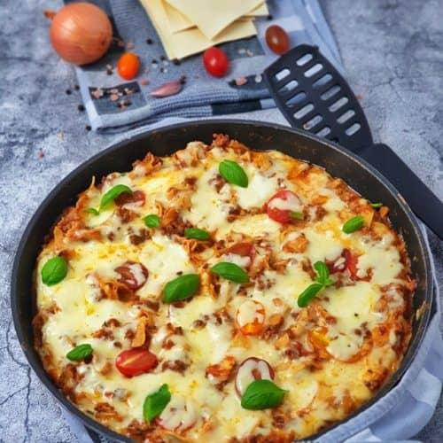 Lasagne aus der Pfanne, ein One Pot Gericht, das in der Pfanne serviert wid. Dekorativ angerichtet und mit Basilikum Blätter garniert fotografiert