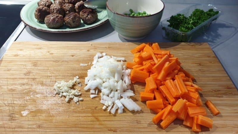 Die Möhren, Zwiebel und Knoblauch klein schneiden.