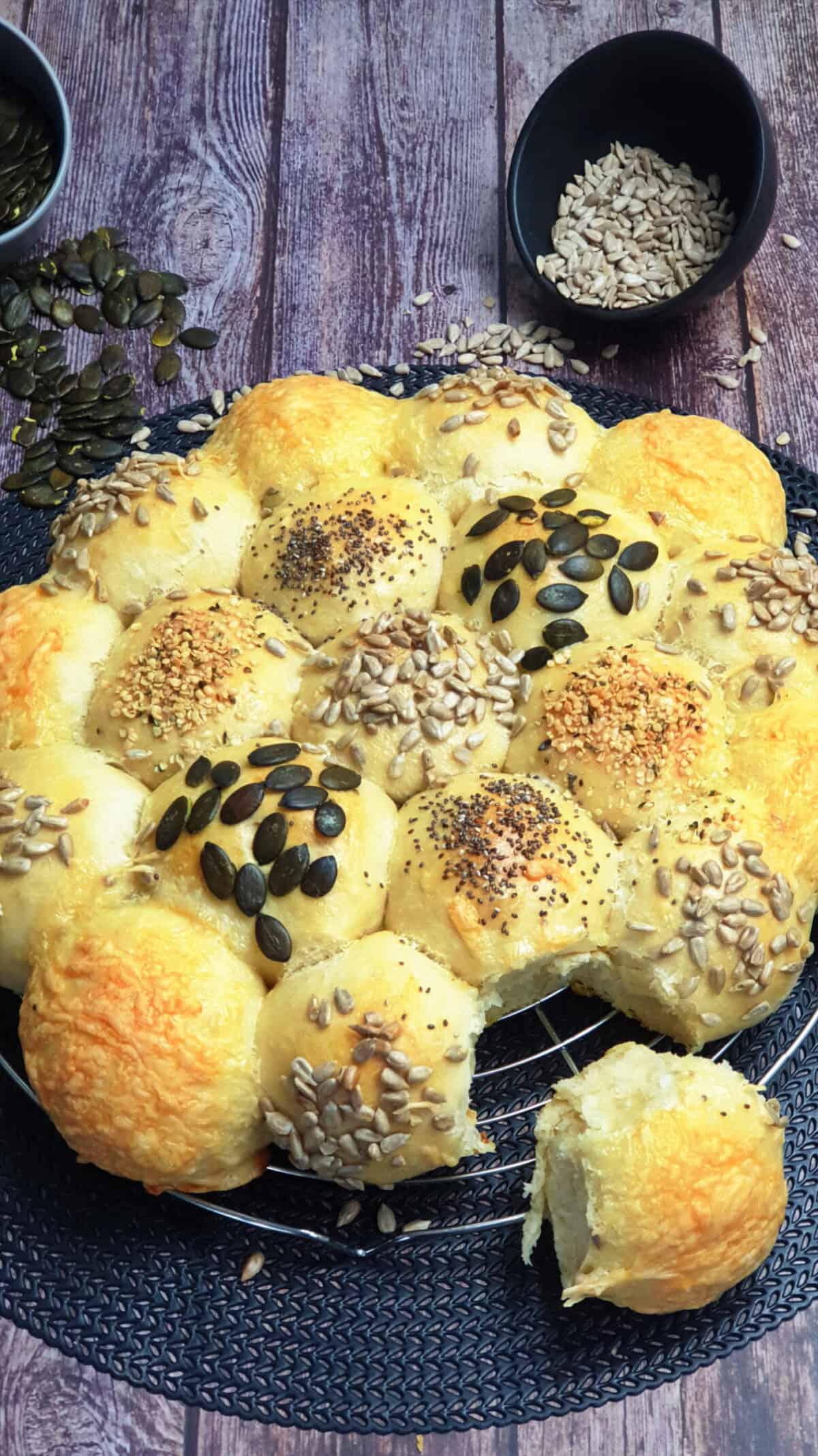 Auf einem großen schwarzen Teller eine Brötchensonne aus Hefeteig mit verschiedenen Toppings aus Körnern und Käse. Im Hintergrund Deko.