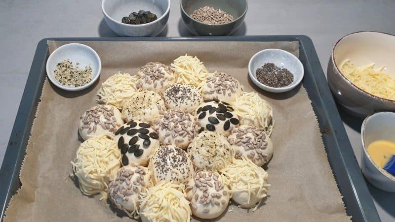 Die Brötchensonne mit verschiedenen Körnern oder Käse bestreuen.