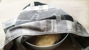 Nach dem Kneten wird der Teig mit einem Handtuch abgedeckt damit er in Ruhe an einem warmen Ort gehen kann.