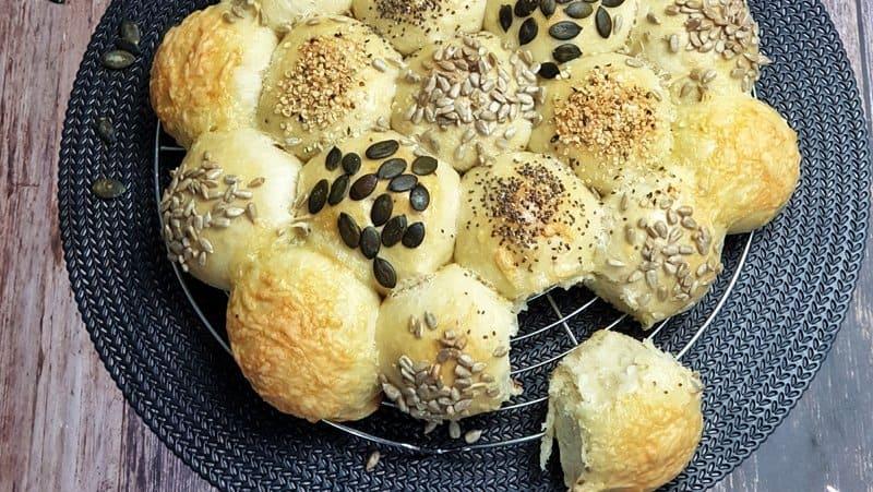 Brötchensonne / Partybrötchen aus Hefeteig dekorativ auf einem Kuchengitter fotografiert. Im Hintergrund 2 Schälchen mit Körnern.