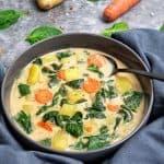 Eine leckere Asiatische Suppe mit Kokosmilch und Spinat in einer grauen Suppenschale dekorativ angerichtet und fotografier