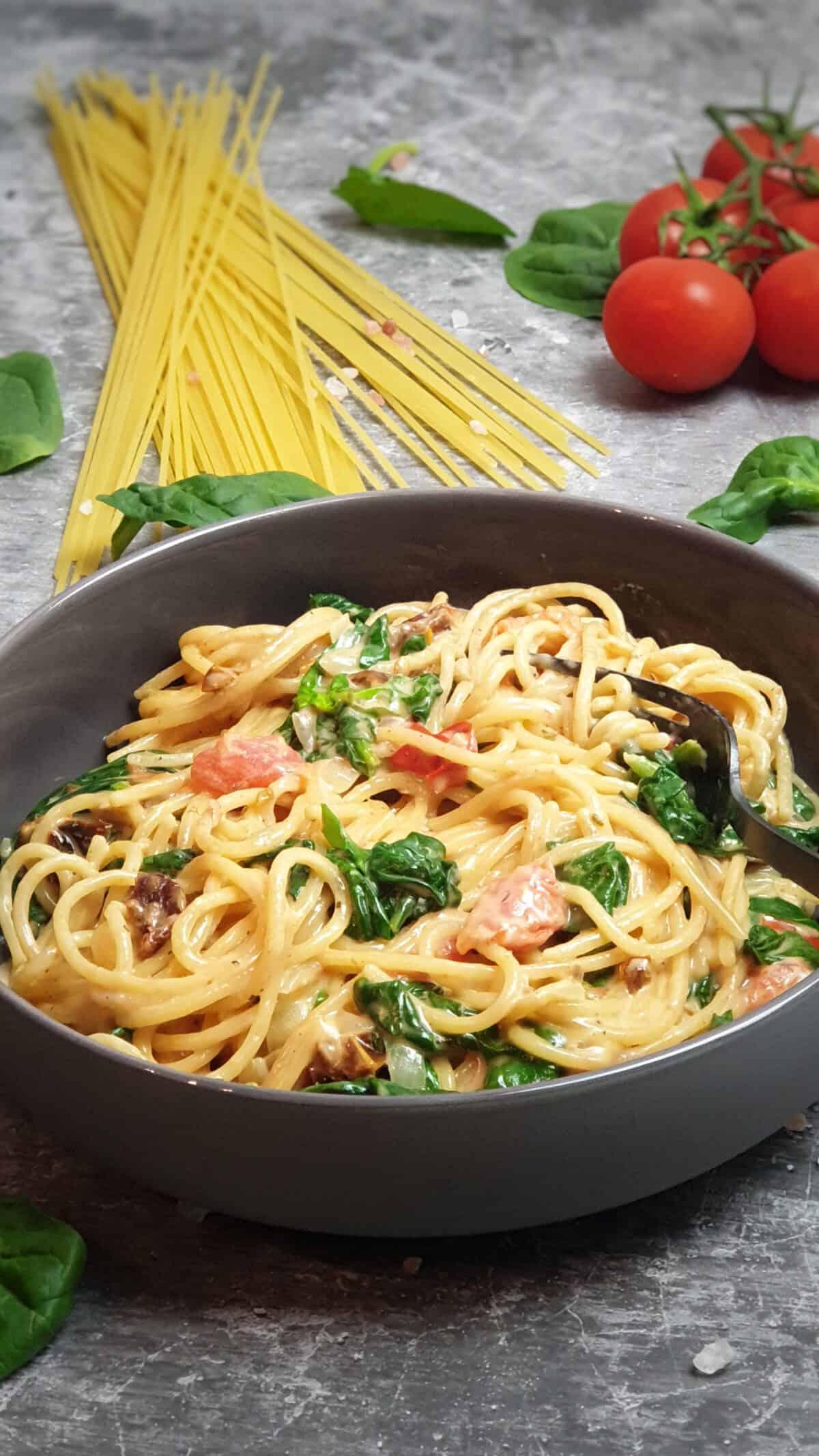 In einer grauen Schale angerichtet One Pot Pasta mit Spinat und Tomaten. Im Hintergrund Deko.