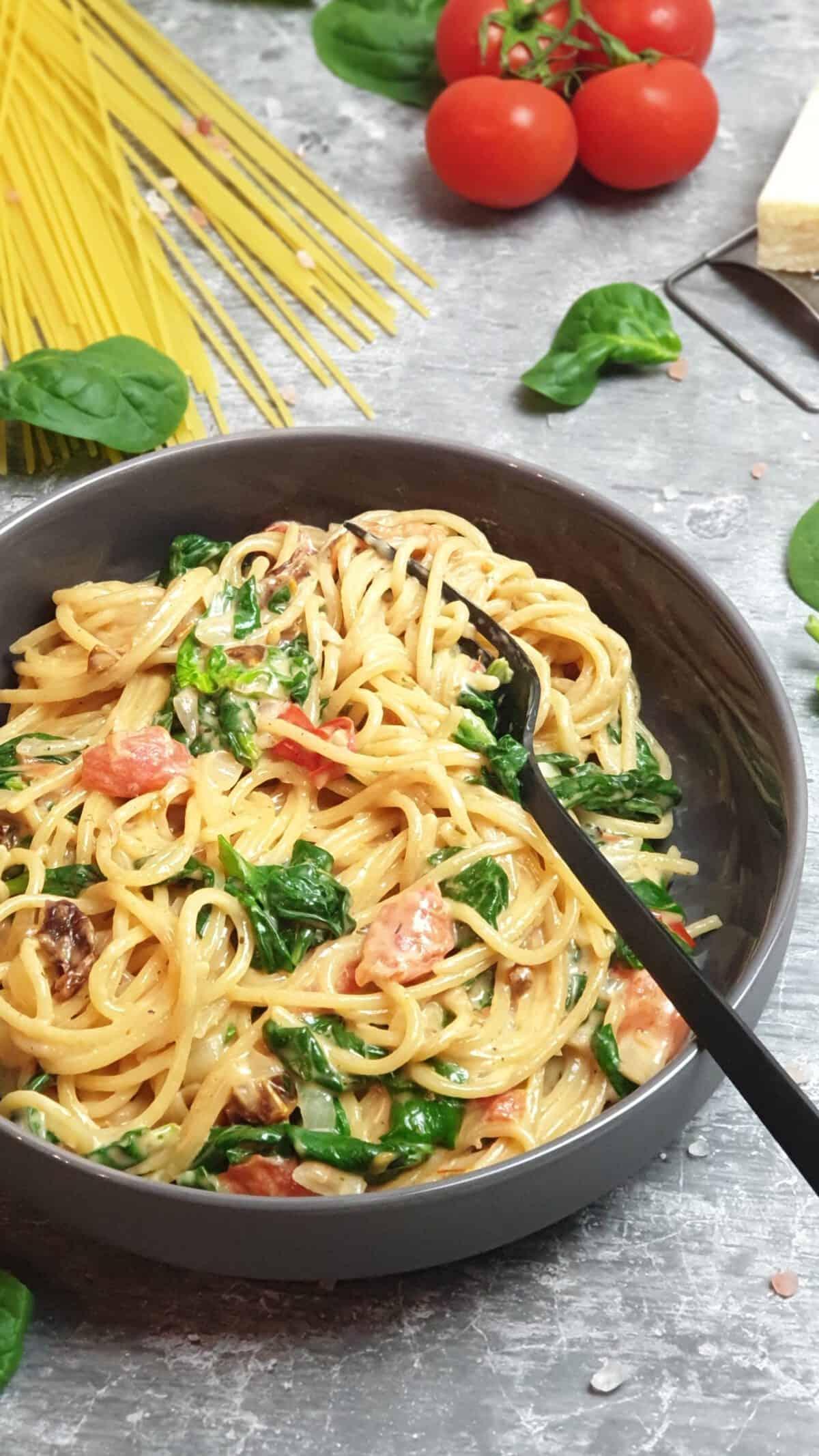 In einer grauen Schale angerichtet Spaghetti mit cremiger Soße und Gemüse. Im Hintergrund Deko.