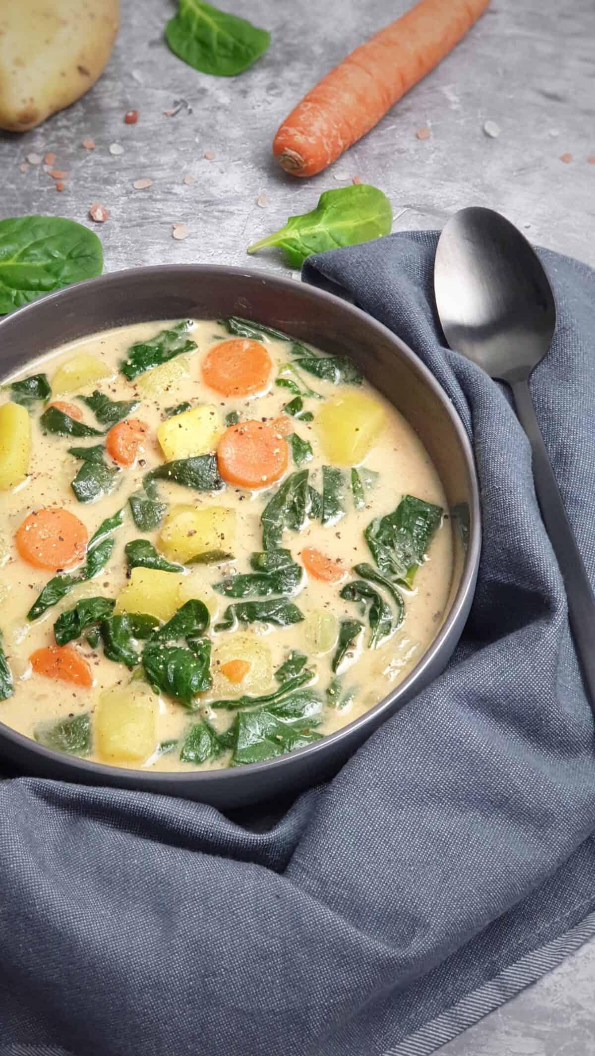 In einer grauen Schale angerichtet asiatische Suppe mit Kokosmilch, Spinat und Gemüse. Im Hintergrund Deko.