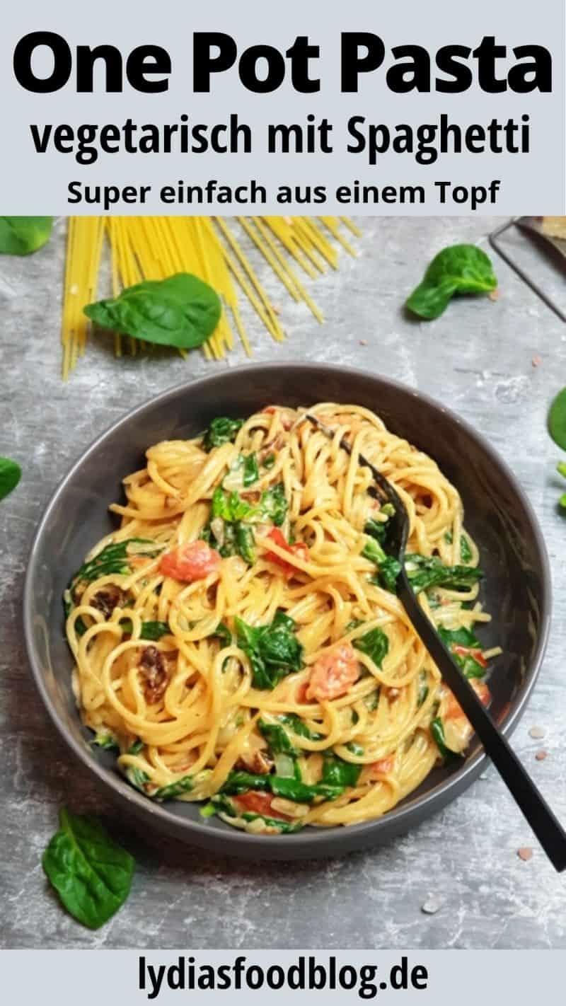 Ein schnelles und leckeres One Pot Pastagericht mit Spaghetti, Spinat und Tomaten angerichtet in einer grauen Schale. In der Mitte der Spaghetti steckt eine schwarze Gabel. Im Hintergrund Spaghetti und Basilikum