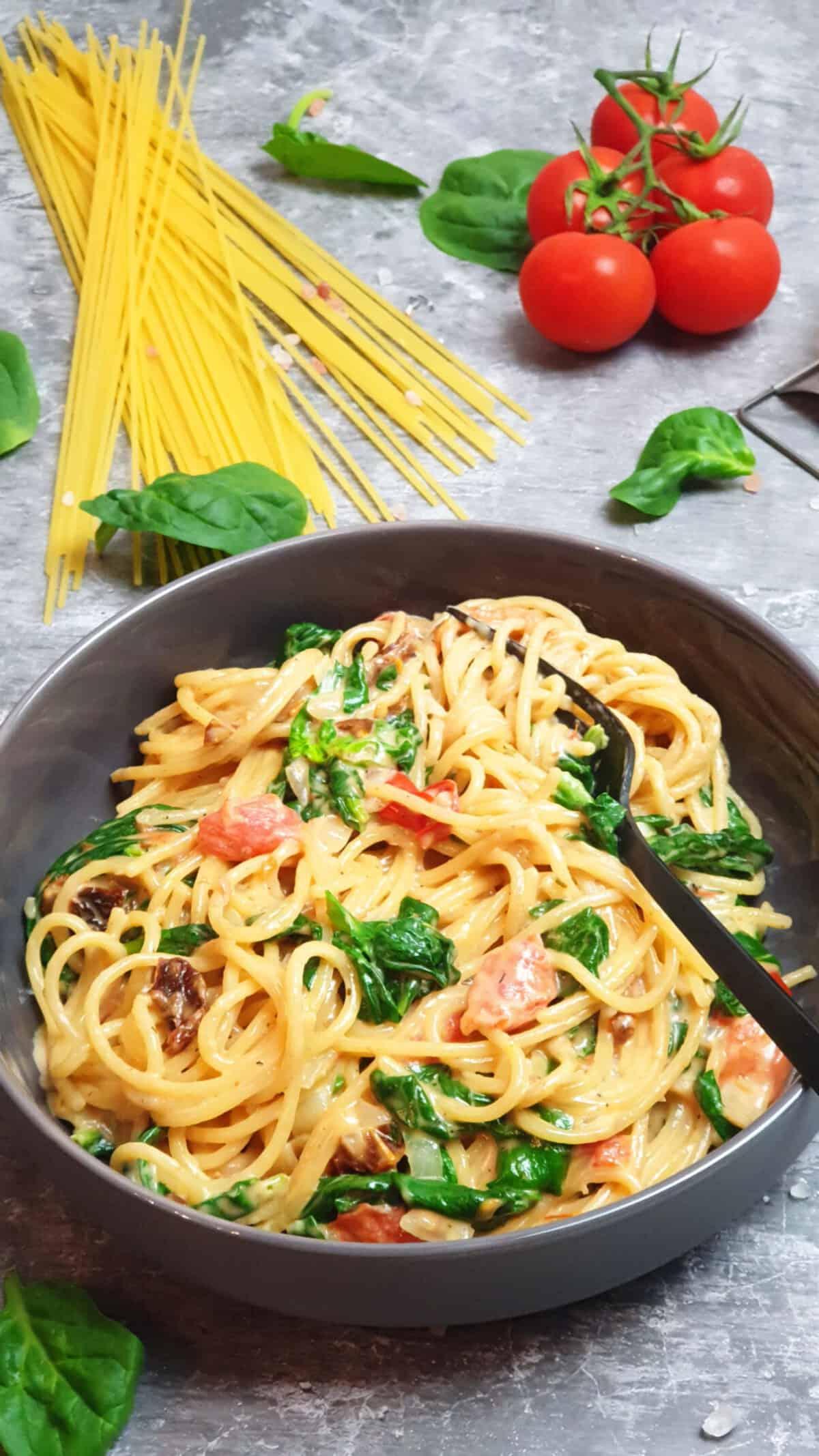 In einer grauen Schale ein One Pot Gericht mit Spaghetti, Spinat und Tomaten.