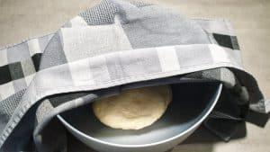 In einer grauen Schale ein Hefeteig mit einem Handtuch abgedeckt.