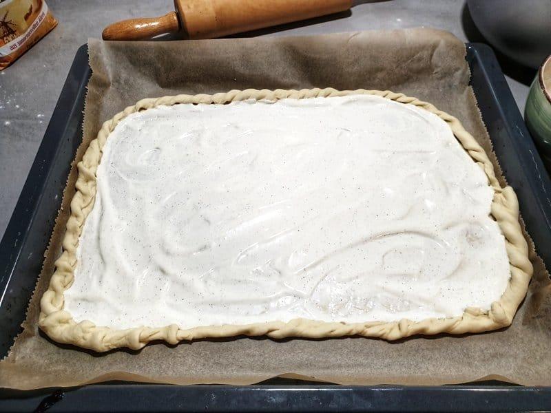 Der Teig für den Flammkuchen kommt auf ein mit Backpapier belegtes Backblech und wird mit Crème fraîche bestrichen.