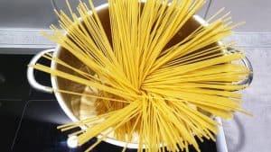 In einem hohen Topf Spaghetti in einer Brühe.