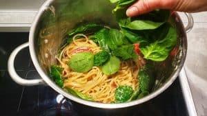 In einem Topf Spaghetti mit Gemüse und frischem Spinat.