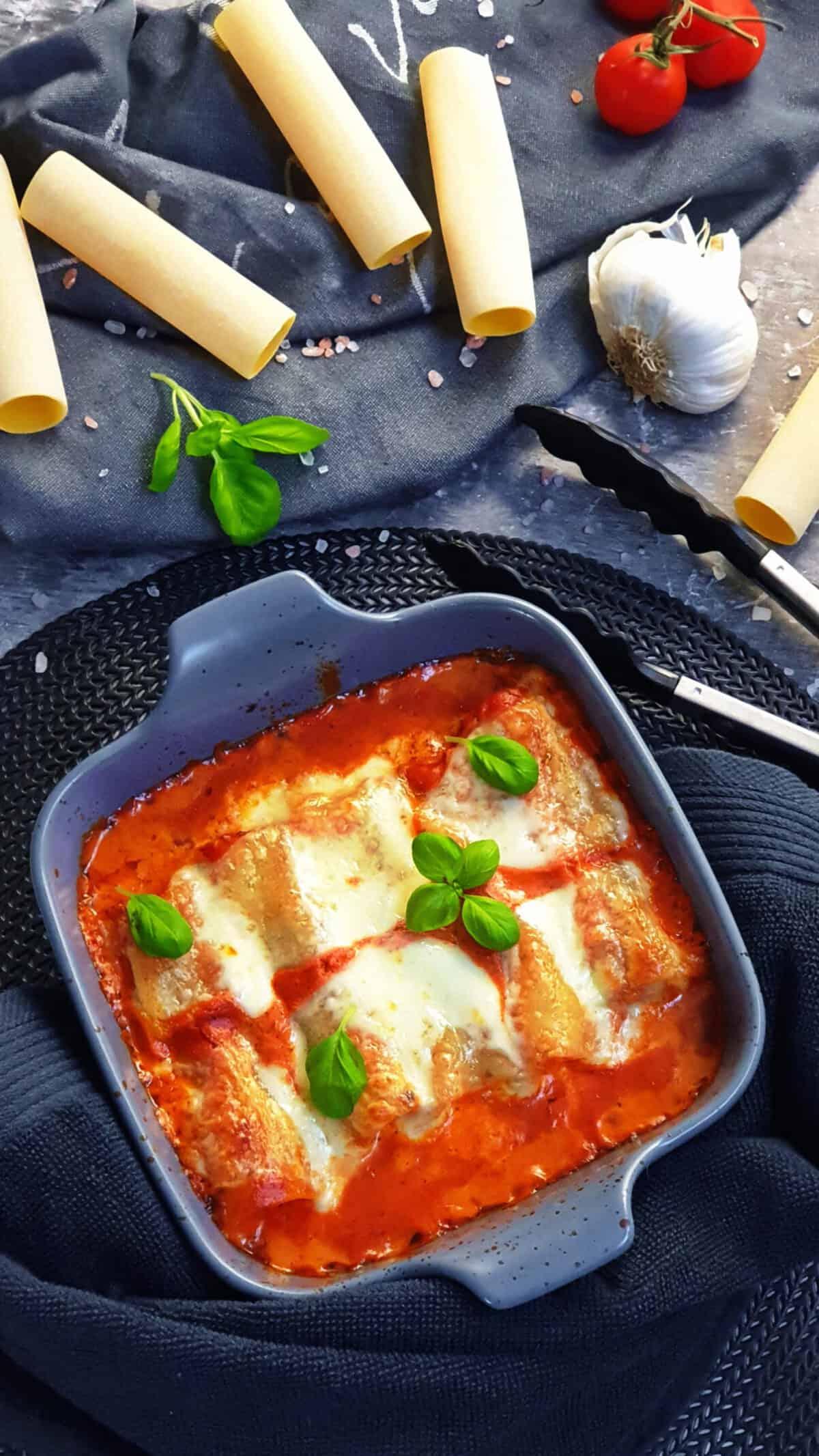 In einer grauen Auflaufform gefüllte Cannelloni mit Hackfleisch in Tomatensoße. Im Hintergrund Deko.