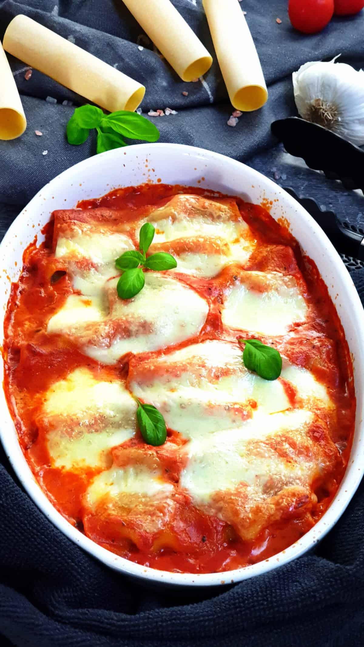 In einer weißen Auflaufform gefüllte Cannelloni mit Hackfleisch in Tomatensoße. Im Hintergrund Deko.