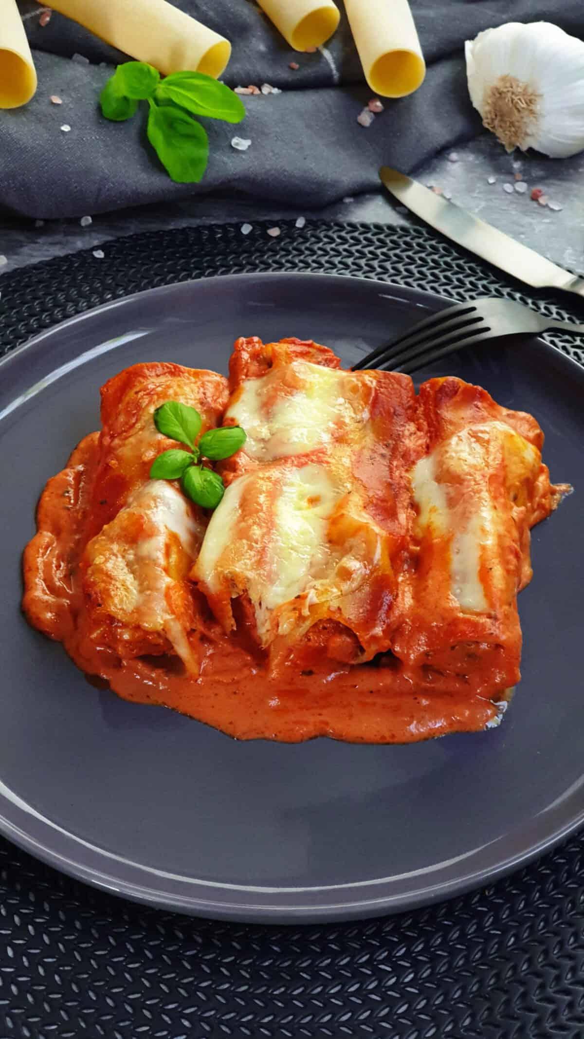 Auf einem grauen Teller gefüllte Cannelloni mit Hackfleisch in Tomatensoße. Im Hintergrund Deko.