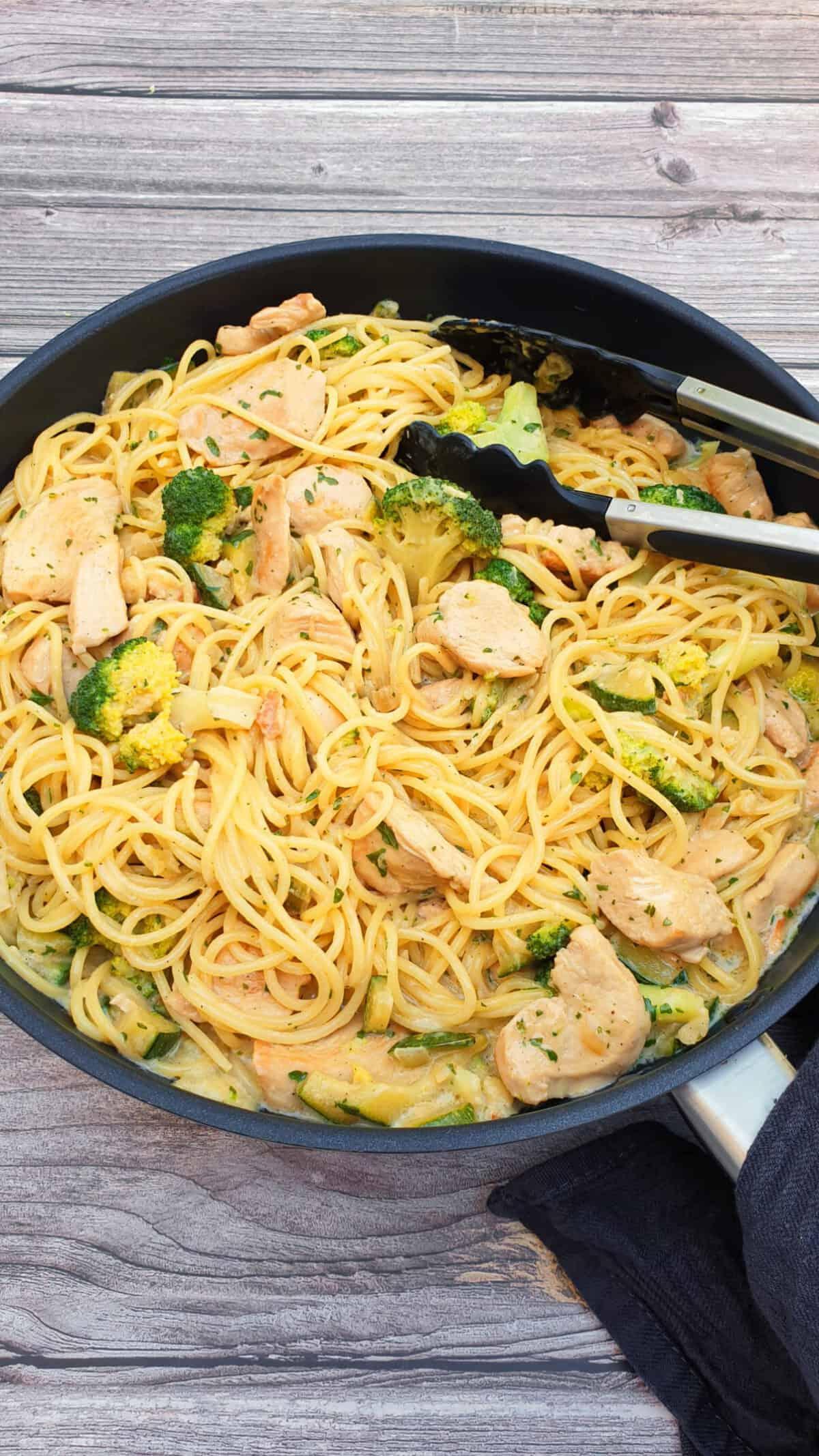 In einer schwarzen Pfanne Chicken Alfredo, ein Nudelgericht mit Hähnchenstreifen, Brokkoli und Zucchini. Mit Petersilie bestreut.