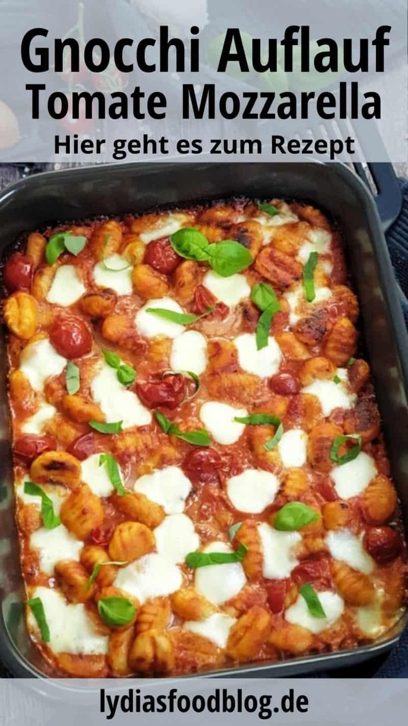 Gnocchi Auflauf mit Tomate und Mozzarella, fotografiert in einer dunklen Auflaufform. Der Auflauf ist mit frischem Basilikum garniert. Im Hintergrund auf einem dunklen Küchenhandtuch dekorativ drapiert, eine Zwiebel, ein paar Strauchtomaten, Knoblauch und Basilikum.