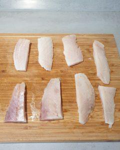 Auf einem Schneidebrett liegt Fisch, in 3x10 cm Streifen geschnitten.