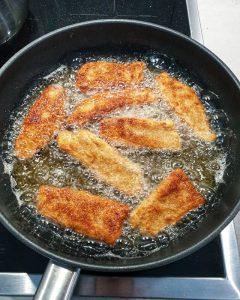In einer Pfanne mit Öl Fischstäbchen, die gebraten werden.