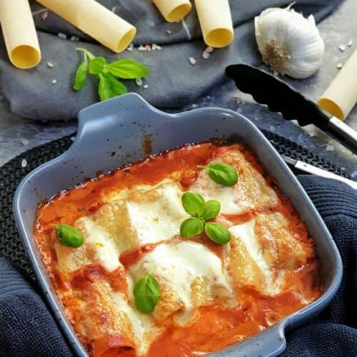 In einer graufarbenen Auflaufform zu sehen, gefüllte Cannelloni mit Hackfleisch und Mozzarella aus dem Ofen in einer Tomatensoße. Im Hintergrund auf einem Handtuch dekorativ Cannelloni Nudeln, Tomaten, Knoblauch und Basilikum drapiert. Neben der Auflaufform zu sehen eine Küchenzange.