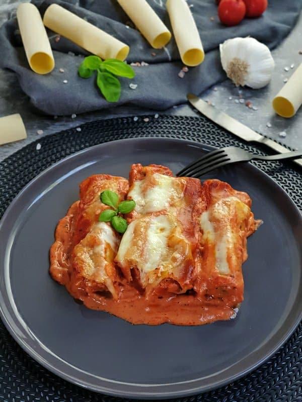 Auf einem dunklen Teller zu sehen, 3 gefüllte Cannelloni in einer Tomatensoße und mit Mozzarella überbacken. Im Hintergrund auf einem Handtuch dekorativ Cannelloni Nudeln, Tomaten, Knoblauch und Basilikum drapiert. Neben dem Teller zu sehen eine dunkle Gabel und ein dunkles Messer in mattschwarz. Fertig sind die Cannelloni mit Hackfleisch und Mozzarella aus dem Ofen.