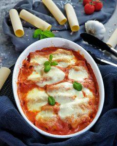 In einer weißen Auflaufform zu sehen, gefüllte Cannelloni in einer Tomatensoße und mit Mozzarella überbacken. Im Hintergrund auf einem Handtuch dekorativ Cannelloni Nudeln, Tomaten, Knoblauch und Basilikum drapiert. Neben der Auflaufform zu sehen eine Küchenzange.