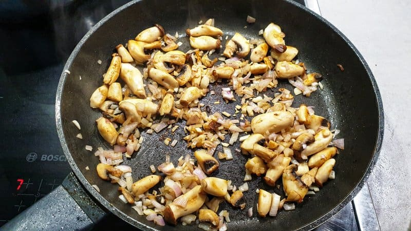 Angebratene Pilze mit Zwiebeln in einer Pfanne.